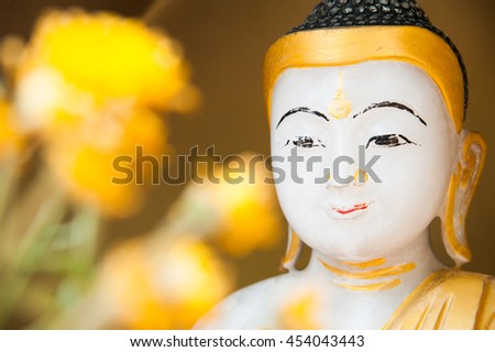 Buddha image of Myanmar with yellow flower in foreground - stock photo