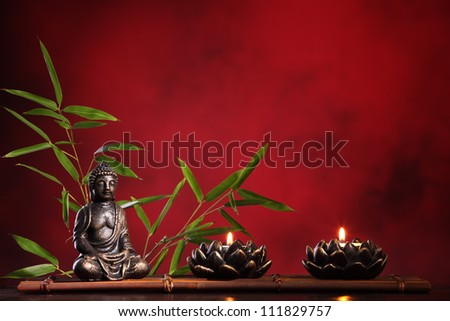 Buddha in meditation with burning candle and bamboo leaf on red background. - stock photo