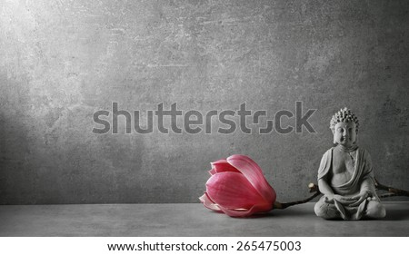Buddha in meditation with magnolia flower - stock photo