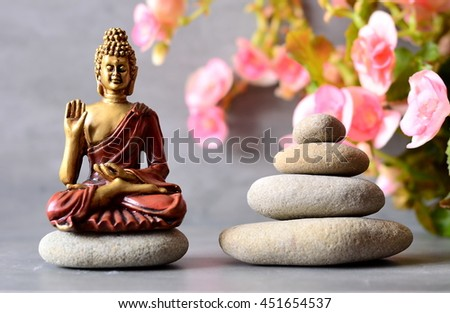 Buddha is sitting  in meditation in ZEN garden with  flower and balance stones. - stock photo