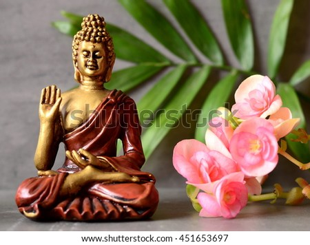 Buddha is sitting in ZEN garden with  flower, palm and balance stones. - stock photo