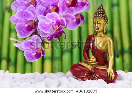 Buddha is sitting in ZEN garden with orchid flower - stock photo