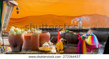 Buddha oblation - Lotus , garland , coconut , colorful silk fabric and incense sticks prepare on the table for pay respect to the buddha. - stock photo