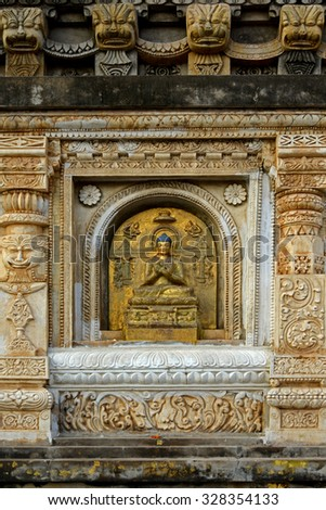 Buddha sculpture at wall Bodh Gaya Buddha Enlightenment place one of the most Buddhist pilgrimage - stock photo