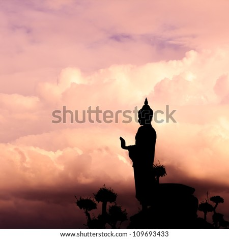 Buddha silhouette on sunset sky. - stock photo