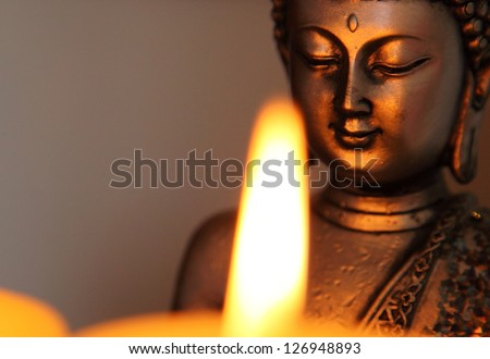 Buddha statue and candlelight - stock photo