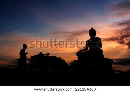 Buddha statue and Novice at sunset in Saraburi, Thailand  - stock photo