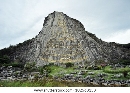 buddha statue carving on mountain in Thailand - stock photo