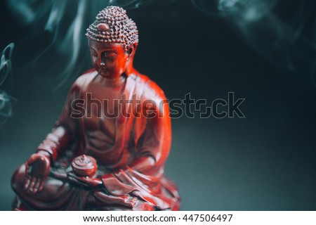 Buddha statue decorated with offerings and flowers. Murti Buddha in the smoke from the incense and floral decorations. Buddhism and its deities, Gautama Buddha FILM TEXTURE  - stock photo