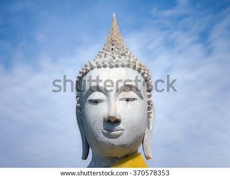 Buddha statue head Against the backdrop bright sky - stock photo