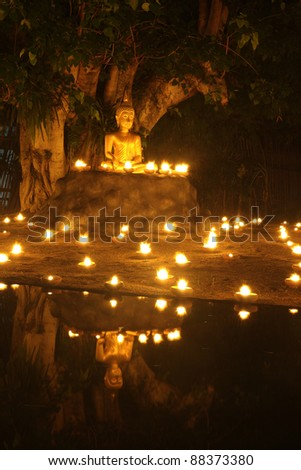 Buddha statue reflect on water with candles fire lighting - stock photo