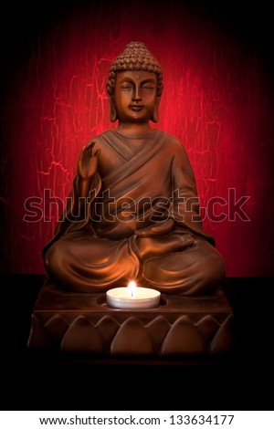 Buddha statue with a candle on a red background - stock photo
