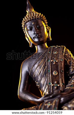 Buddha statue with glow against black background - stock photo