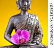 Buddha statue  with orchid against golden background - stock photo