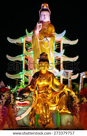 Buddha statues decorated with beautiful flower and colorful led lights at a buddhish Temple during wesak day at Kuala Lumpur Malaysia. - stock photo
