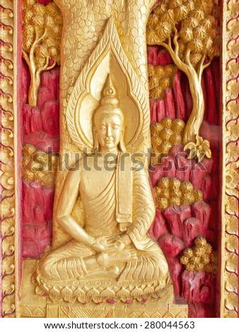 Buddha wooden carving painted  red and gold color on window temple, Thailand - stock photo