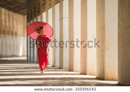 Buddhism novice is walking with umberella in temple - stock photo