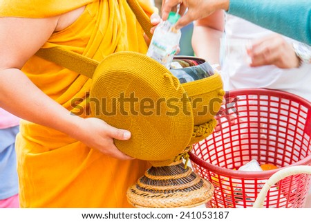 Buddhist Monk gets offerings in the morning - stock photo