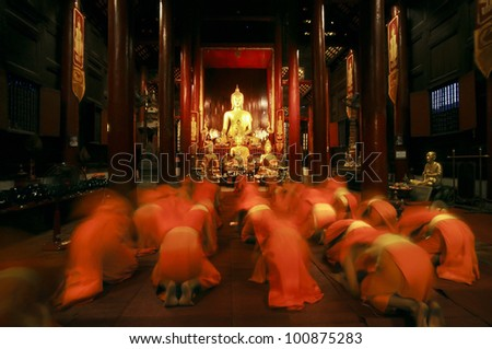 Buddhist monk kneels down prayer in temple - stock photo