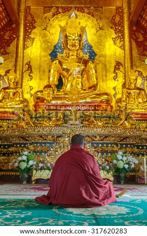 Buddhist monk sitting down in meditation pose inside the chapel  - stock photo