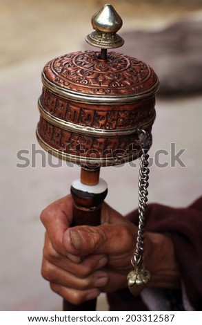 Buddhist monk with a prayer wheel in Thiksey monastery, close-up hand and prayer wheel, Ladakh, India - stock photo