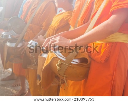 Buddhist monks and Buddhist novices waiting for food offering in foggy morning, Thailand - stock photo