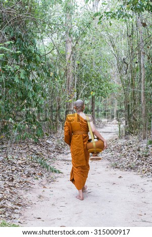 Buddhist monks walking in the jungle - stock photo