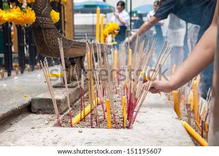 Buddhist people pray using incense and candle - stock photo