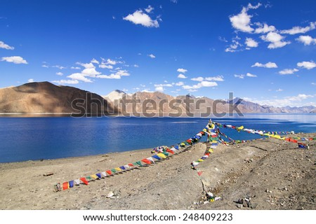 Buddhist prayer flags flying at Pangong tso (Lake). It is huge lake in the Himalayas situated at a height of about 4,350 m (14,270 ft). It is 134 km (83 mi) long and extends from India to Tibet. - stock photo