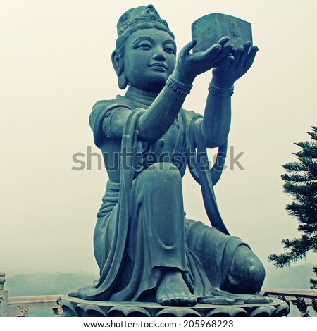 Buddhist Statue praising the Big Buddha (Tian Tan Buddha) on Lantau island (Hong Kong).Square image, instagram effect - stock photo