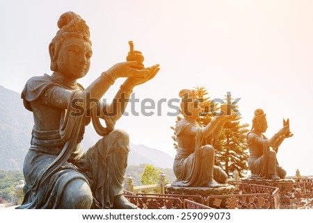 Buddhist statues praising and making offerings to the Tian Tan Buddha (the Big Buddha) in sunlight at Lantau Island, in Hong Kong. Hong Kong is popular tourist destination of Asia. - stock photo