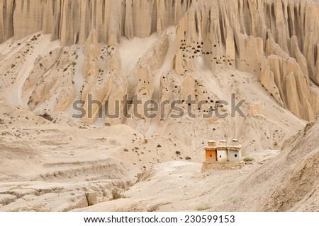 Buddhist stupa and ancient human settlement in mountain, Mustang, Nepal - stock photo