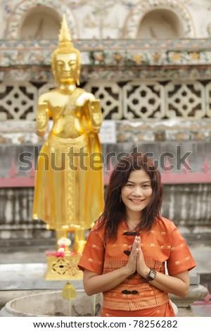buddhist thai woman in traditional dress praying near golden buddha statue - stock photo