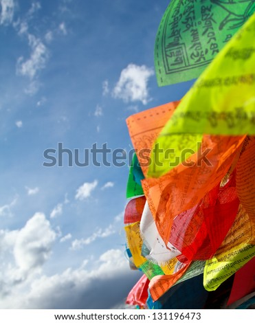 Buddhist tibetan prayer flags flying with blue sky - stock photo