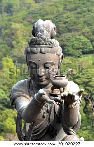 Buddhistic statue praising and making offerings to the Tian Tan Buddha at Po Lin Monastery, Lantau Island - stock photo
