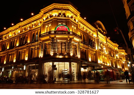 BUENOS AIRES, ARGENTINA - MARCH 25, 2011: Colorful illuminated Galerias Pacifico (Pacific Gallery) building - famous landmark with street vendors in Cordoba Avenue - stock photo