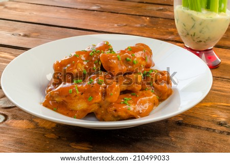 Buffalo chicken hot wings with mayonnaise sauce and celery - stock photo