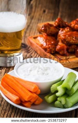 Buffalo chicken wing with cayenne pepper  sauce served hot with celery sticks and carrot sticks with blue cheese dressing for dipping and beer - stock photo