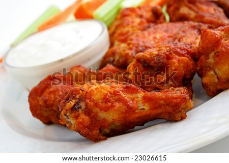 Buffalo chicken wings on plate with blue cheese sauce, carrots, and celery. - stock photo