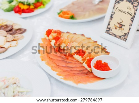 Buffet table served with mediterranean food. Assorted fish, salmon, shrimp and red caviar with cheese - stock photo