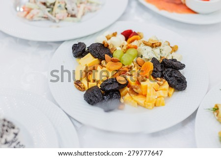 Buffet table served with tasty meals. Cheese platter garnished with dried fruits - stock photo