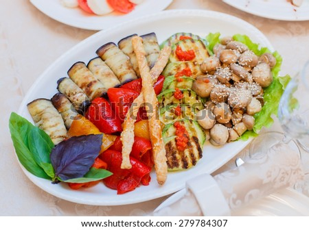 Buffet table served with tasty meals. Mixed vegetables grilled, eggplant, zucchini, sweet pepper, mushrooms, basil and sauce. Holiday banquet menu - stock photo