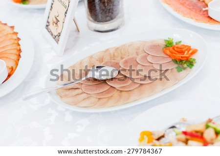Buffet table served with tasty meals. Sliced of neat tongue aspic with green fresh parsley and orange carrot. Holiday banquet menu  - stock photo