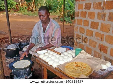 BUIKWE REGION, AJIJJA, UGANDA - JULY 26: An unidentified village baker bakes cakes  on July 26, 2004 in village Ajijja, Uganda. - stock photo