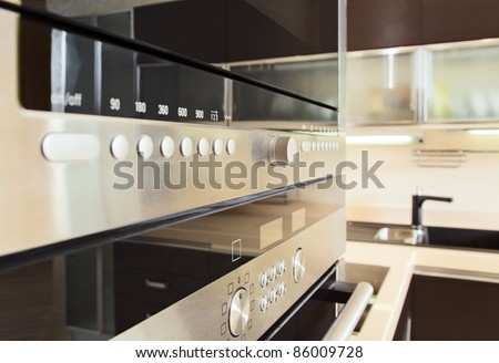 Build in microwave oven in modern kitchen interior with hardwood furniture - stock photo