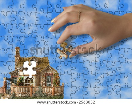 Build the house - hand bring piece of house (puzzle) - stock photo
