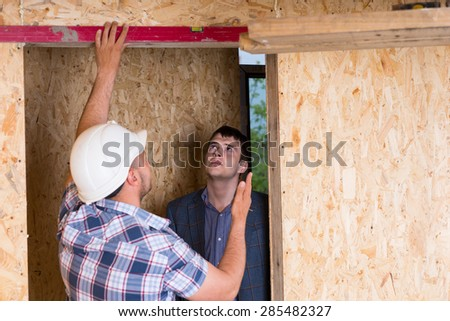 Builder and Architect Inspecting Construction of Door Frame with Level Inside Unfinished Home with Exposed Particle Plywood Boards - stock photo