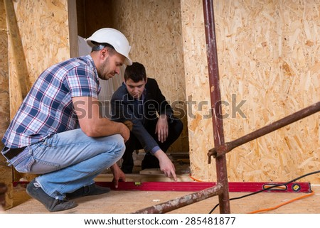 Builder and Architect Working Together and Inspecting Even Level of New Home Doorway Inside Building Construction Site, for Accuracy and Quality Control - stock photo