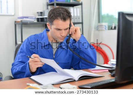 Builder checking through is notes over the phone - stock photo
