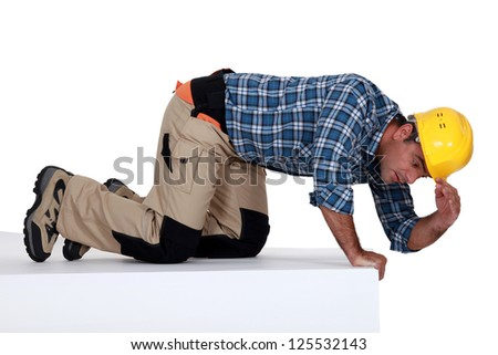 builder climbing on wall being curious - stock photo